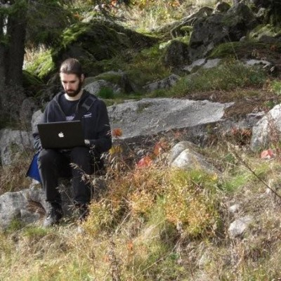 Photo of Ingmar sitting on a rock in a pine forest with eyes focused on his grey mac laptop